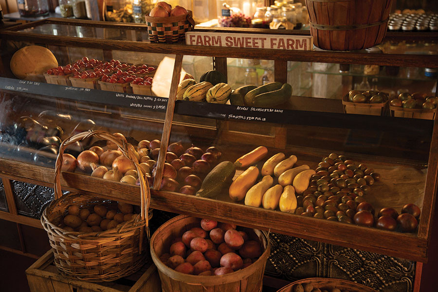 A large display case and several baskets containing seasonal fruits and vegetables of all different shapes, sizes, and colors