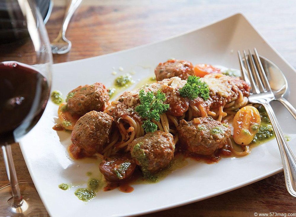 A plate of traditional Italian spaghetti and meatballs garnished with parsley next to a glass of red wine