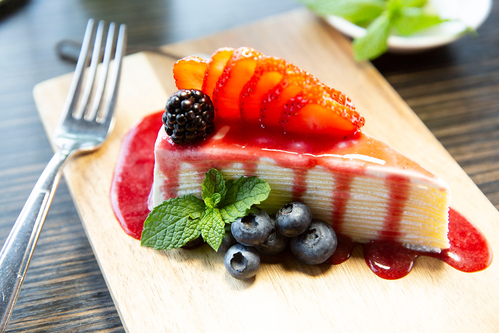 Layer Crepe Cake with Raspberry Sauce and fresh berries and a mint garnish