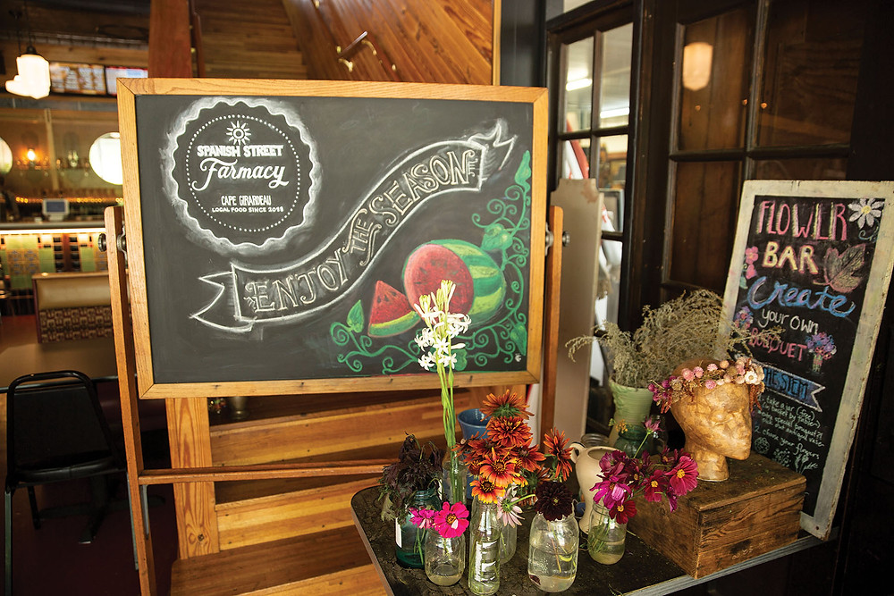 A large black board with colorful fruit pictures and the words spanish street farmacy, enjoy the season, sits behind many vases of wild flowers