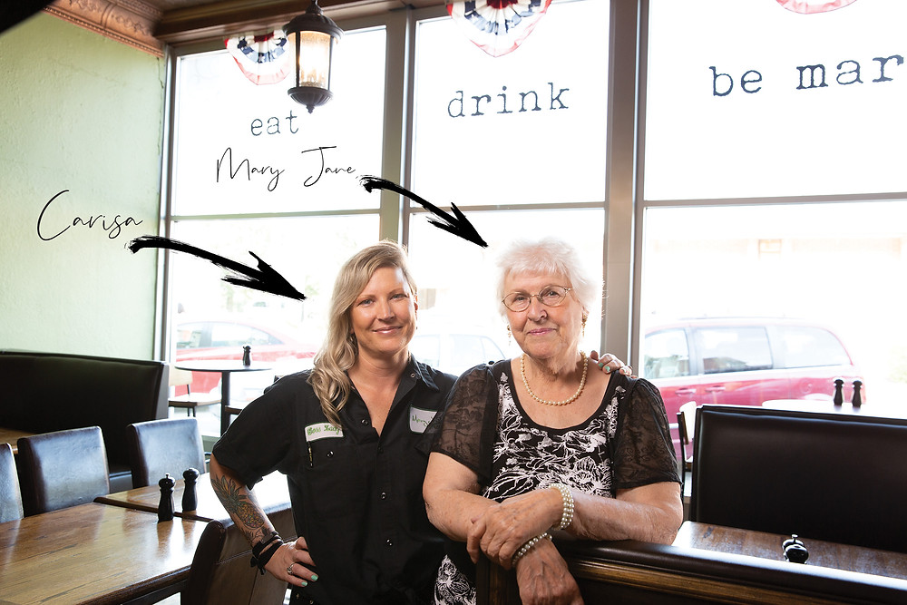 """A beautiful woman stands with her lovely grandmother in front of a huge window that says """"eat. drink. be mary"""""""