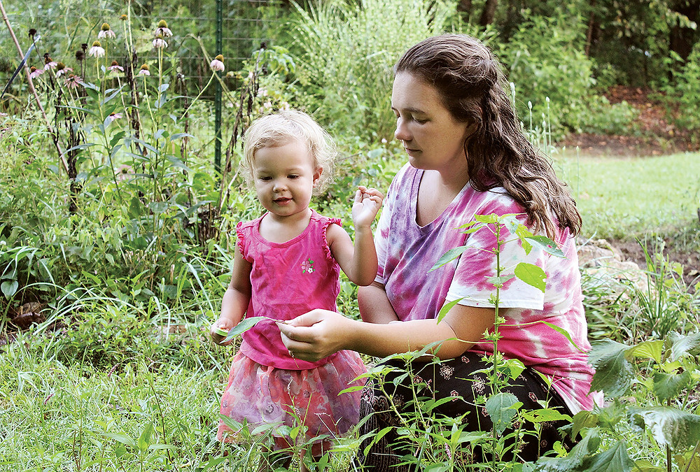 A baby girl discovers natures treasures as her mother shows her a leaf in a wild garden