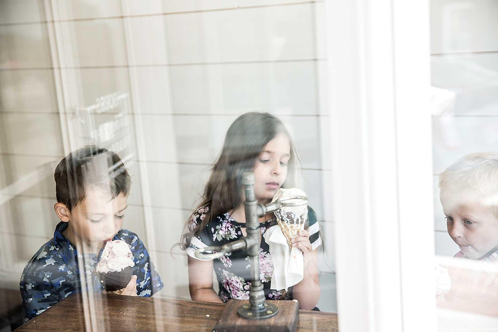 3 beautiful children enjoy their ice cream treats as they sit in the large front window of Sugar Chic Creamery
