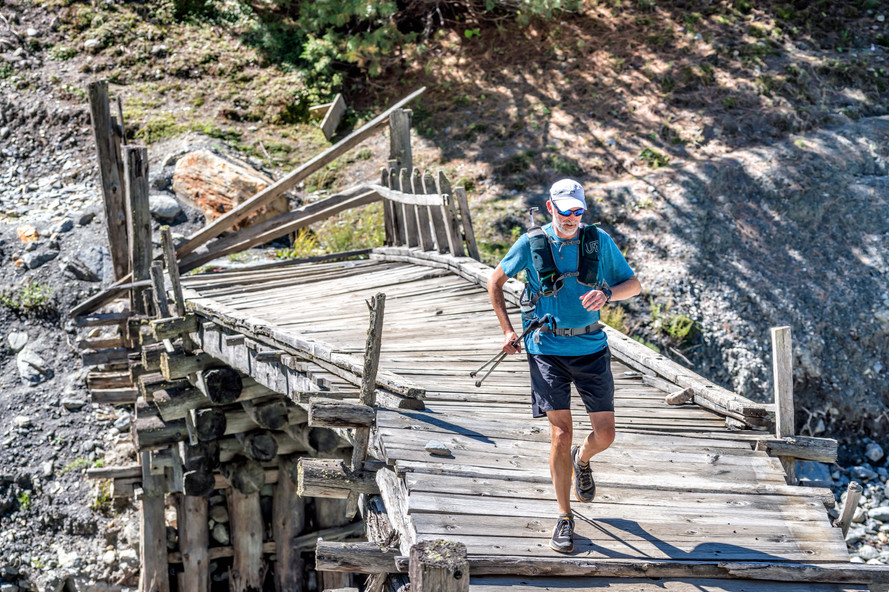 Russ Trice crossing a bridge in the mountains