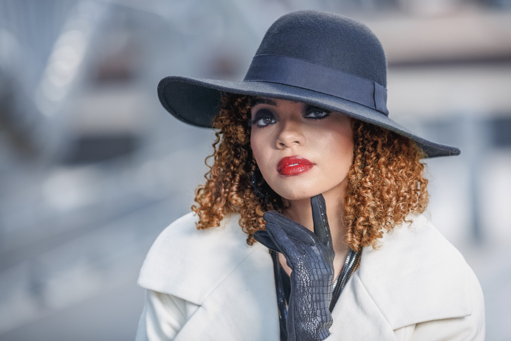 M. Flowers is ready for the city in her black wide brim floppy hat, cream coat and black gloves.