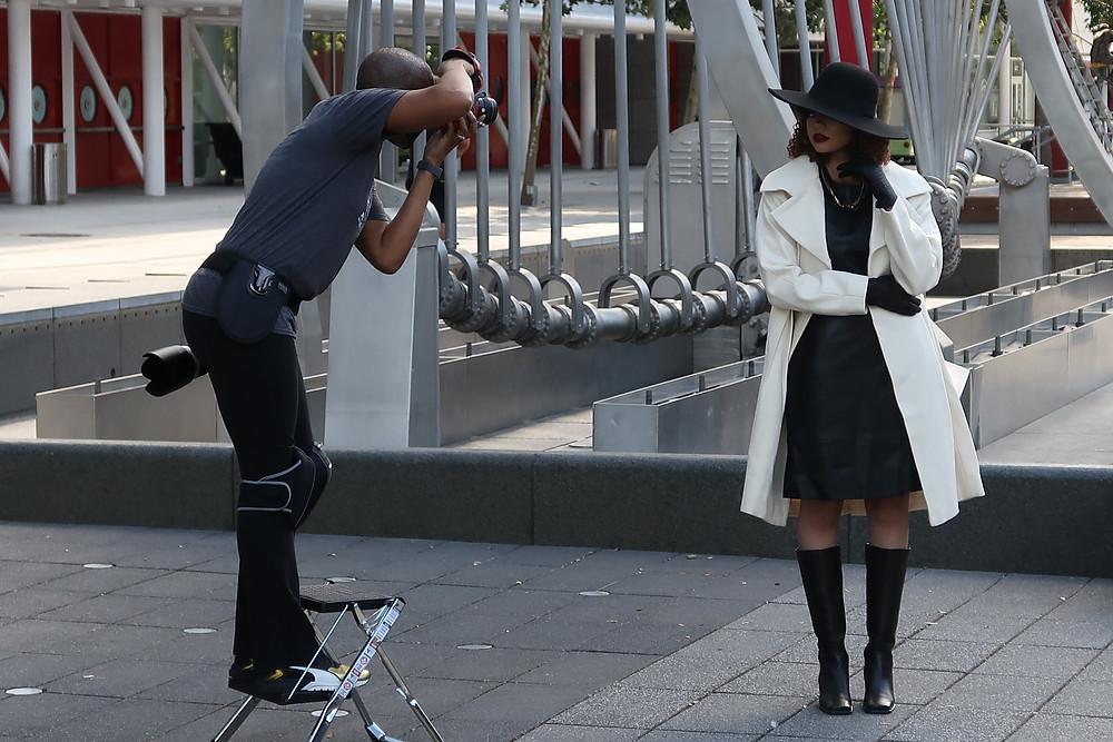 G carefully perches on a step stool while capturing her client during a photo session in downtown Houston.