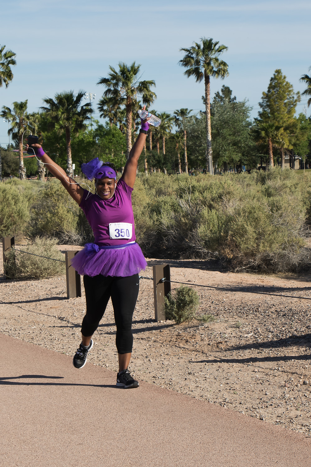 Purple 7k runner with hands in the air
