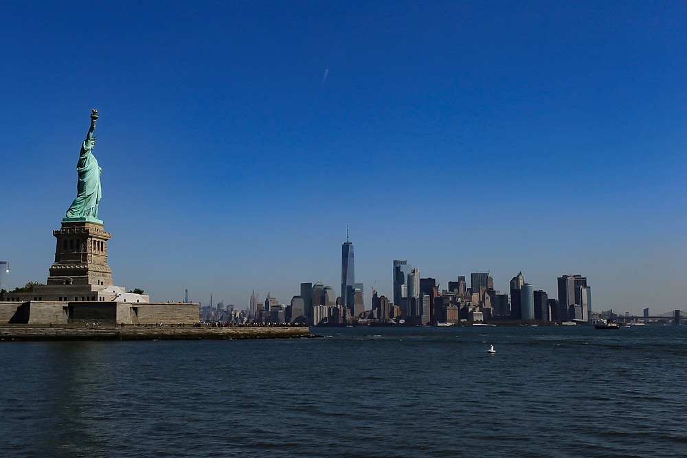 Statue of Liberty and lower Manhattan in the distance from the water.