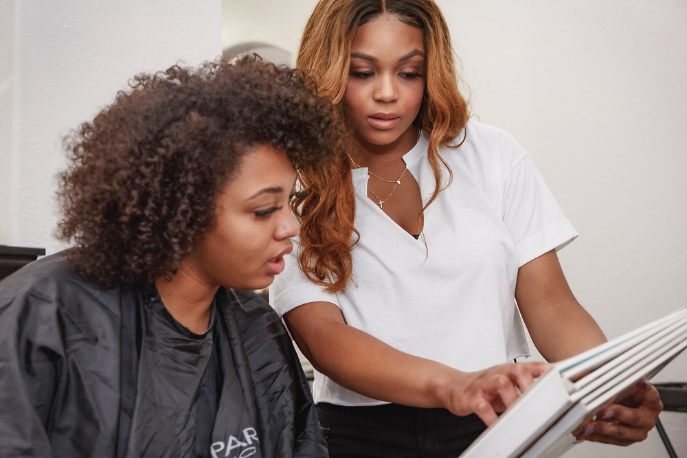 Mariah reviews a color chart with her client to help her decide what's the best color option for her new style.
