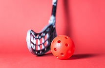 Floorball stick and ball against red bac