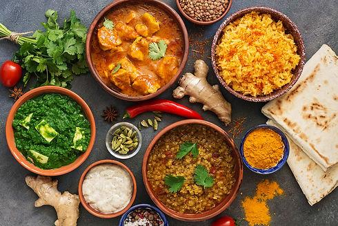 Assorted Indian food on a dark rustic ba