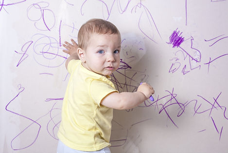 Baby boy drawing with wax crayon on plas