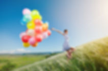 Happy woman with balloons running on the