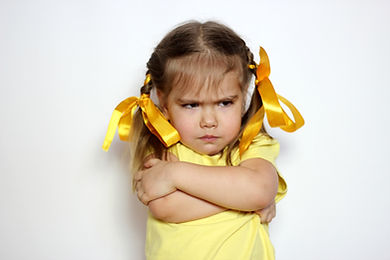 Angry little girl with yellow bows and y