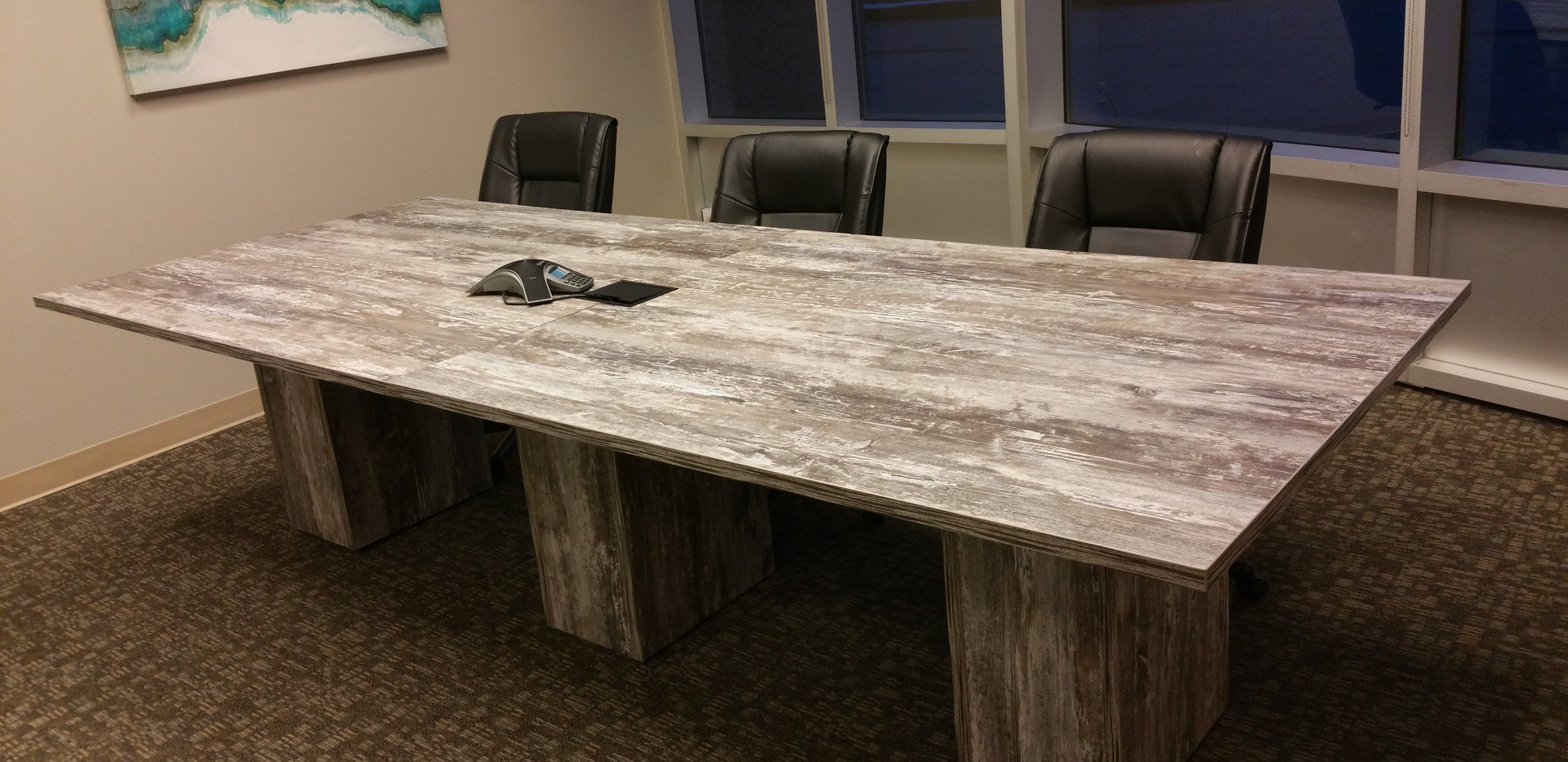 10' conference table in intrigue laminate with matching supporting panel based legs and a data port