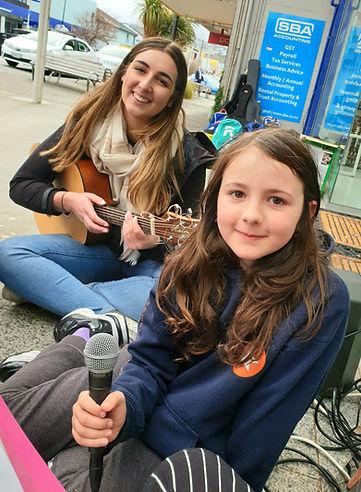 Guitar teacher and guitar pupil busking