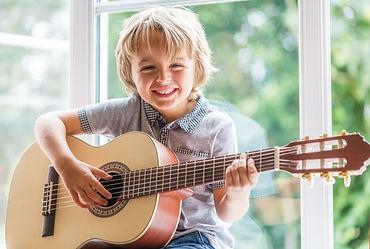 BOY PLAYING GUITAR IN THE SUN