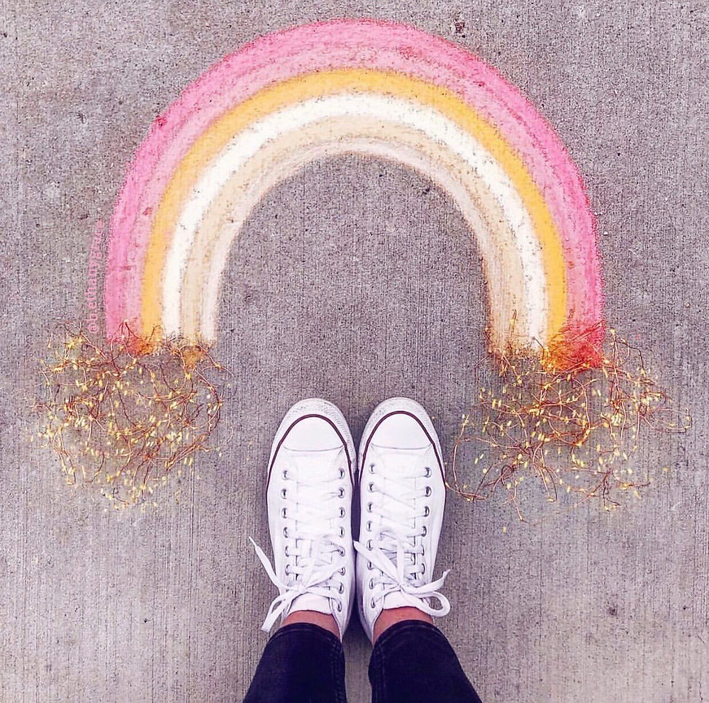 person's feet in front of a rainbow on the ground