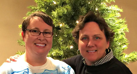Two smiling women in a citizen advocacy relationship in front of a decorated tree