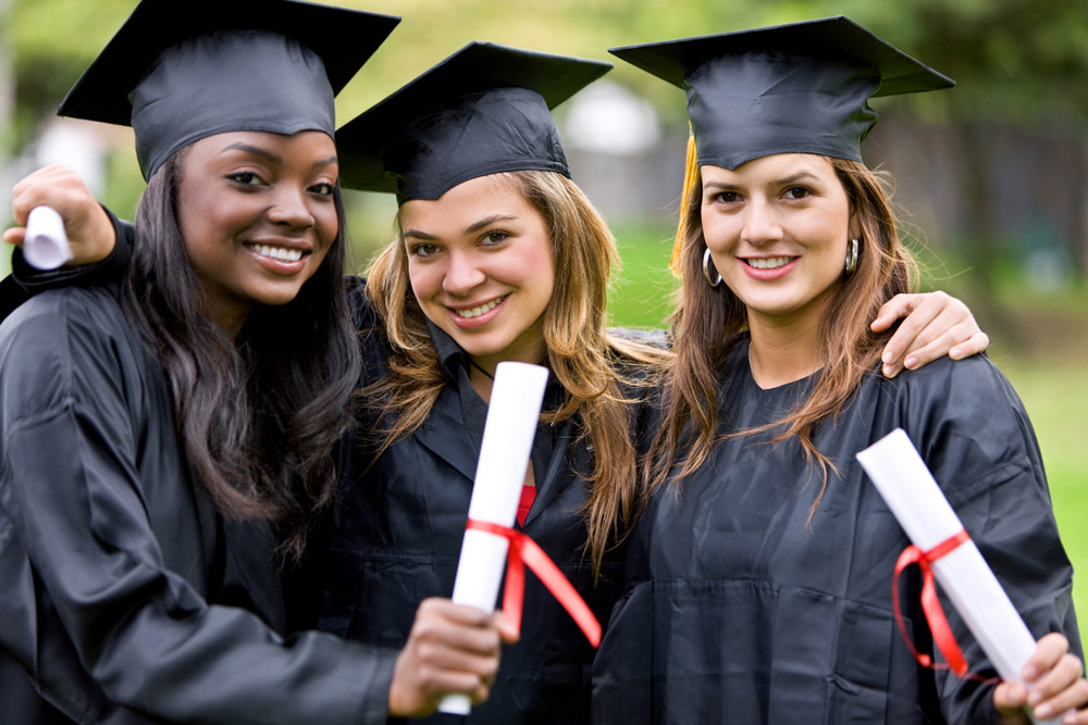 Picture of 3 young, female university graduates in caps and gowns holding their diplomas.
