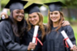 Stock photo of tree girls of different ethnicity in black caps and gowns holding diplomas