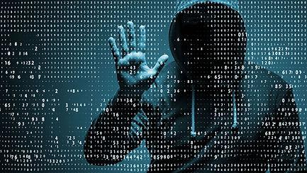 hooded figure behind glass screen covered in binary code