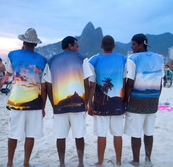 Vendedores de Mate com uniformes le modiste originals em Ipanema com o Morro Dois Irmãos Pôr do Sol em Ipanema Aplauso