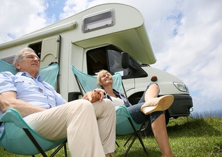 Senior couple relaxing in camping folding chairs, camper in background-1