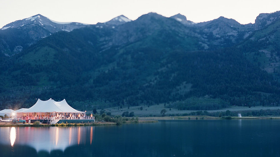 White wedding tent on a lake in front of the Grand Teton mountains