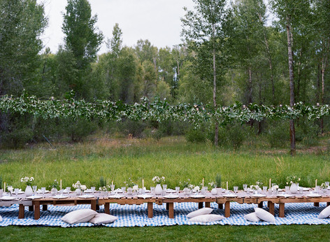 Long Wooden Table in a Field with White and Green Flowers, Candles and Pillows on the Ground