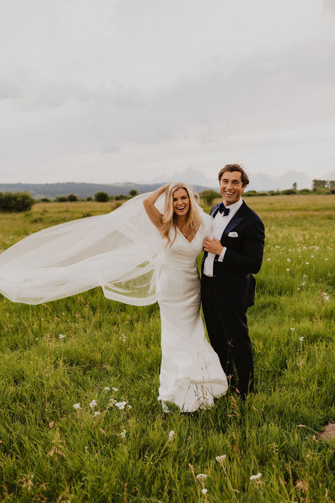 Bride and Groom Standing in a Field with the Bridal Veil Floating in the Wind
