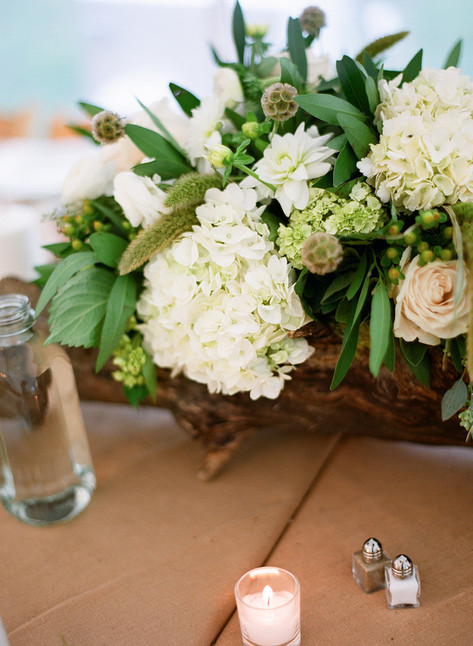 Flower Arrangement with White Hydrangea and Greenery in a Wooden Log