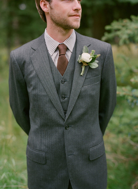 Groom Looking in the Distance with a Suit and White and Green Boutonniere