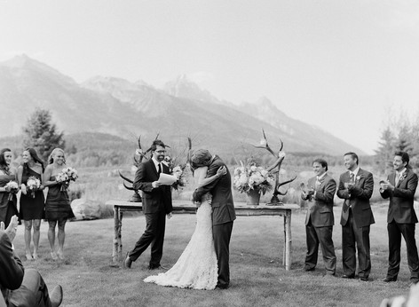 Bride and Groom Hugging in front of Altar Table with the Teton Mountains in the Background
