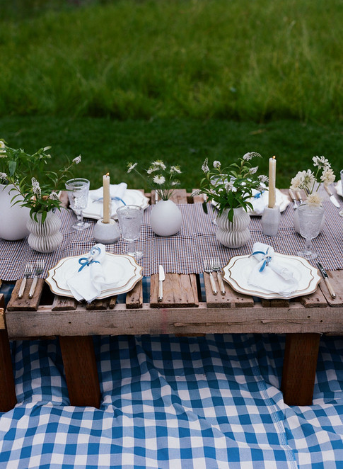 Tablescape with Burgundy and Blue Checkered Table Runner, Small White and Stone bud vases with white flowers and herbs, and White Marble Candstick Holders