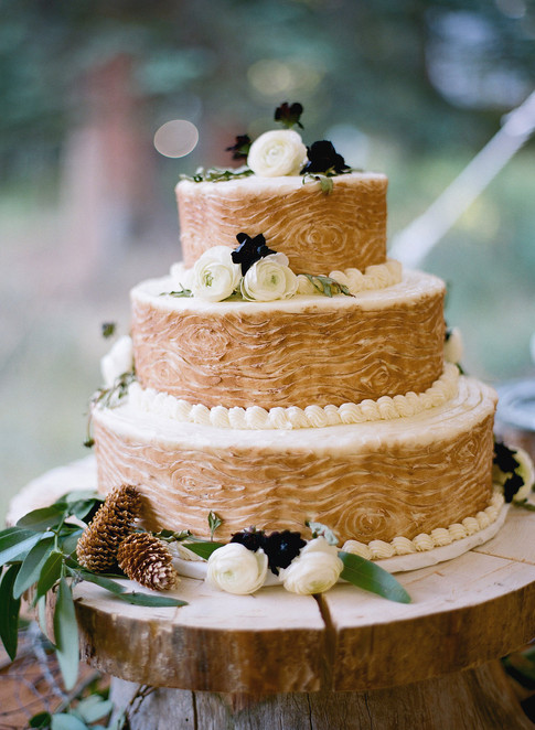 Three Tiered Wedding Cake with Brown Icing in a Wood Pattern with Pinecones and White Ranunculus