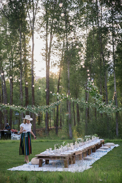 Women in a Colorful Striped Skirt Walks up to a Long Low Table in a Field