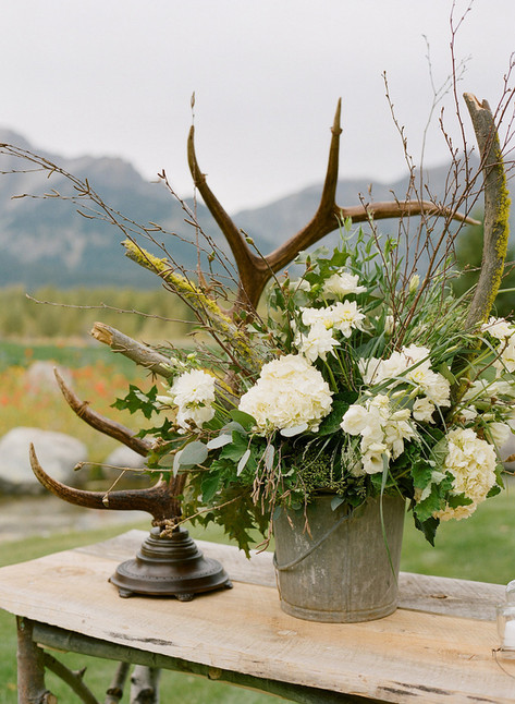 Rustic Metal Bucket with White Hydrangeas, Greenery and Branches next to a Large Standing Antler