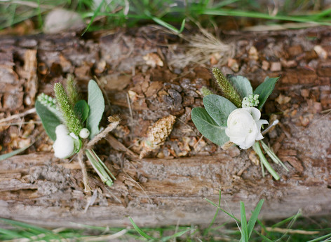 Two White and Green Boutonnieres laying on a Wooden Log