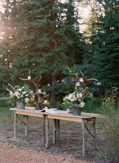 Rustic Wooden Table with Antlers, White and Green Flower Arrangments in fron tof Tall Evergreen Trees