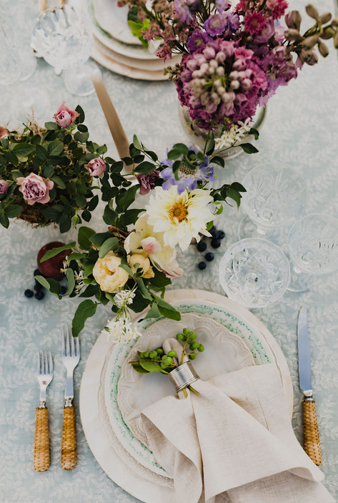 Tablesetting with Light Blue Patterened Tablecloth, Cream and Green Plates, Cream Napkins Arranged with Green Berries, Woven Straw Silverware and Pink and yellow Flowers and Greenery