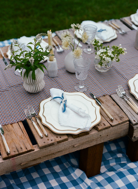 Placesetting with White and Gold Rimmed Scallop Plate and White Napkin Tied iwth a Blue Shoelace Ribbon