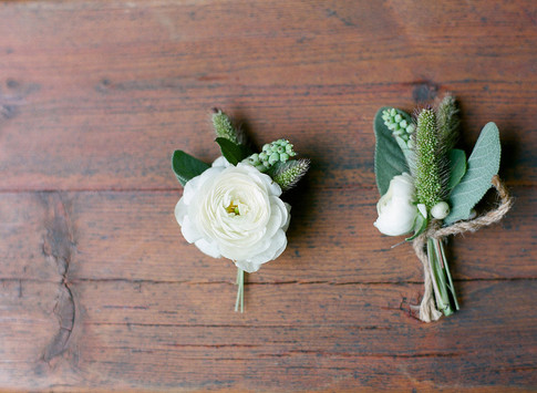 Two White and Green Boutonnieres on a Wooden Table