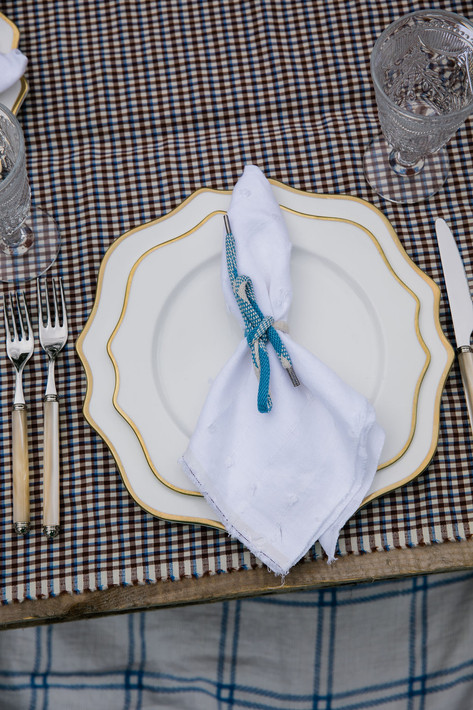White and Gold Rimmed Scalloped Plates with White Napkins tied with a Blue Shoestring and Pearl Handled Flatware