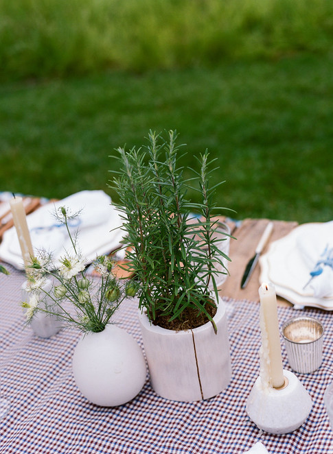 Rosemary in a stone container with flowers in a round stone Container and white marbel candle holders on a Burgundy and Blue Checkered Table Runner