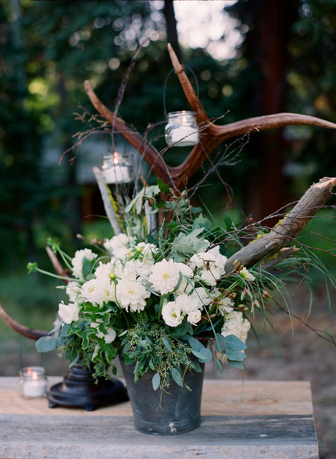 White and Green Flower Arrangement in a Metal Bucket with Antlers Behind with Hanging Candles