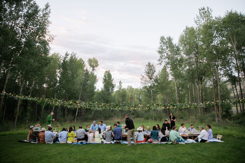 People Sitting at a Low Low Table in a Field in the Distance