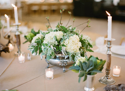 Brown Table with White and Green Flower Arrangment in a Silver Bowl with Horn and Silver Candlesticks
