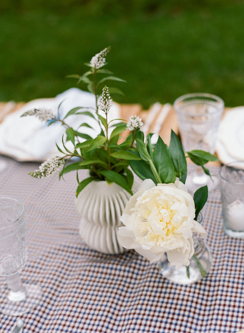 White Veronica and a White Peony in Small Bud Vases on a Burgundy and blue Checkered Table Runner