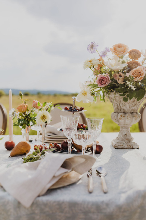 Romantic tablesetting with Tan Candlesticks, Tall Flower Arrangments in Stone Containers, Small Silver bud vases and Pears and Grapes on the Table